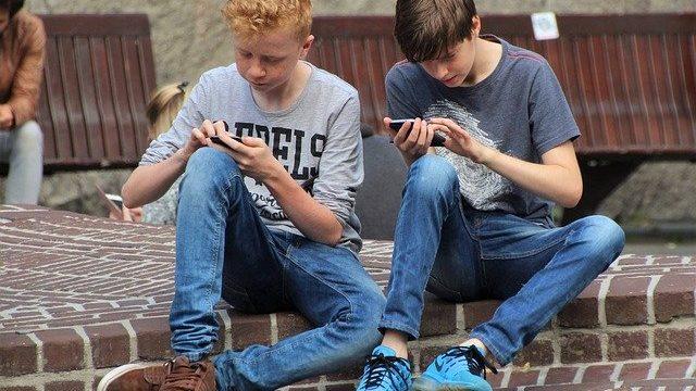 スマホゲームしている少年2人